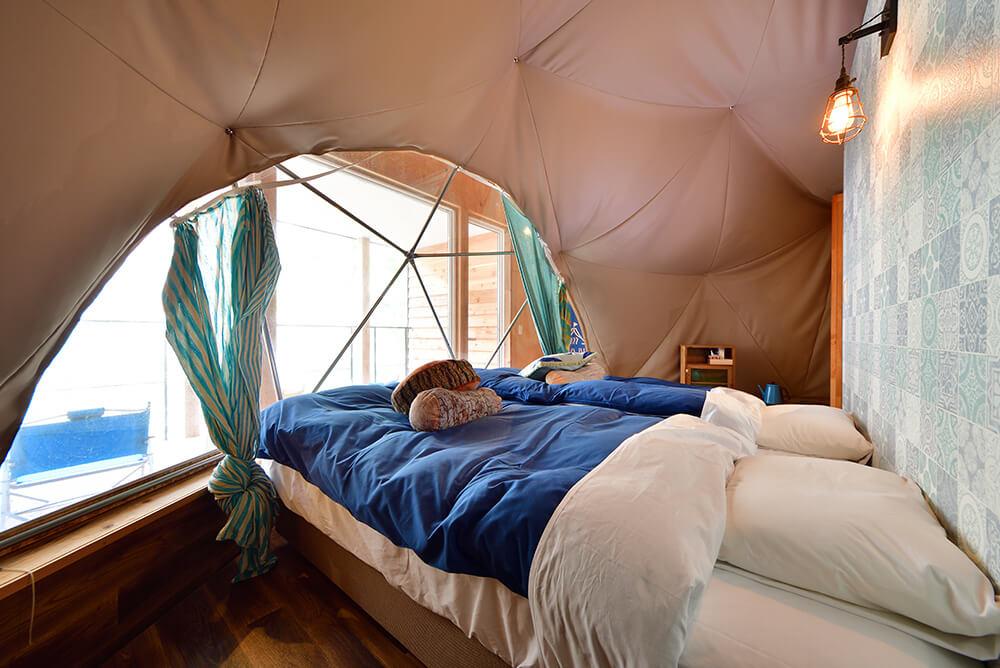 ドームテントの中、広々ベットでゆっくりできます。ウッドデッキから星空も眺めれるグランピングシマブルー