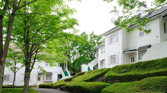 高原リゾート「那須高原TOWAピュアコテージ」白くて清潔感のある建物。緑あふれるコテージ。